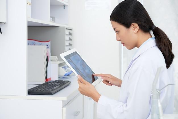 Aziatische vrouwelijke arts die de schedelröntgenstraal van de patiënt bekijken op tablet in bureau