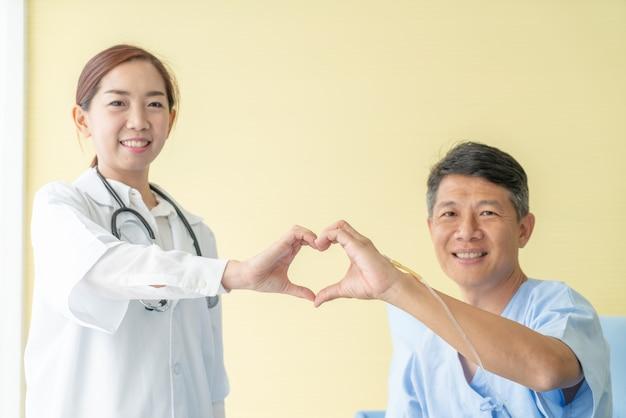 Aziatische vrouwelijke arts die en hart scheert met de hand met hogere patiënt glimlacht maakt