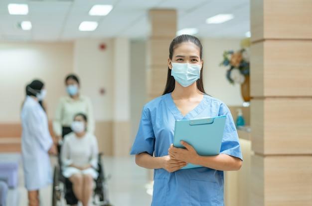 Aziatische vrouwelijke arts die gezichtsmasker draagt tijdens het werken in het ziekenhuis