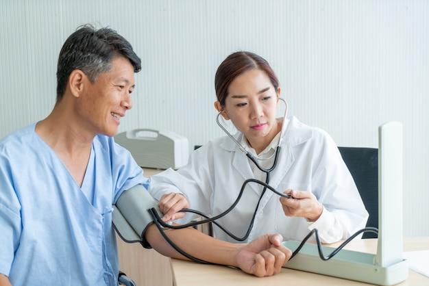 Aziatische vrouwelijke arts die haar patiënt ckecking
