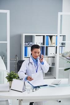 Aziatische vrouwelijke arts die op mobiele telefoon in bureau spreekt en verslagen bekijkt