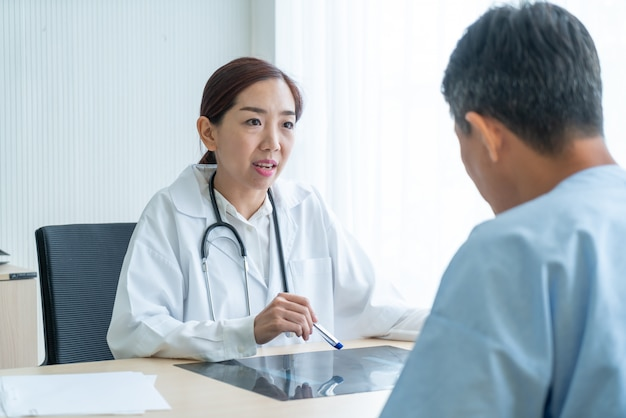 Aziatische vrouwelijke arts en patiënt bespreken iets zittend aan tafel