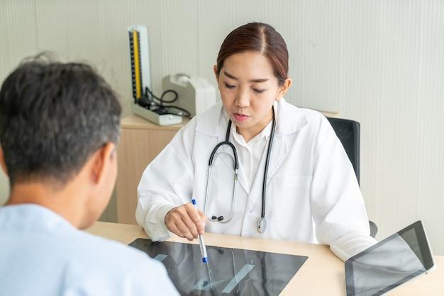 Aziatische vrouwelijke arts en patiënt die iets bespreken terwijl het zitten bij de lijst