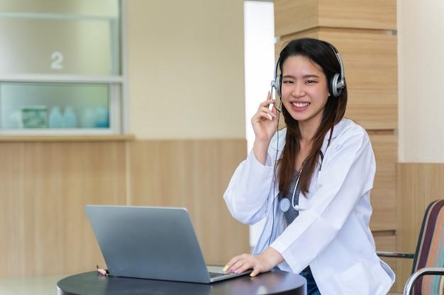 Aziatische vrouwelijke arts in headset die haar headset-microfoon online belt voor een pijnpatiënt