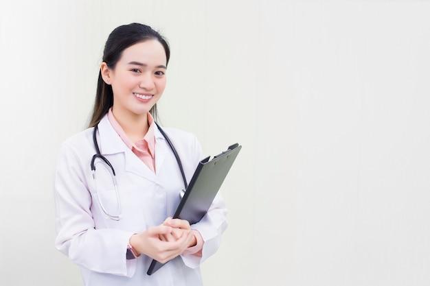 Aziatische vrouwelijke arts in witte laboratoriumjas houdt documentklembord in haar hand en kijkt naar de camera in het ziekenhuis.