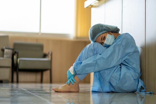 Aziatische vrouwelijke arts met een chirurgisch gezichtsmasker zittend op de vloer moe van het werk vanwege de impact van een pandemie-uitbraak van covid-19, droefheid vrouw in de gezondheidszorg, medisch en gezondheidszorgconcept