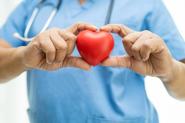 Aziatische vrouwelijke arts met rood hart in verpleegafdeling, gezond sterk medisch concept