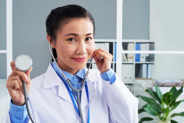 Aziatische vrouwelijke arts poseren met stethoscoop in kliniek