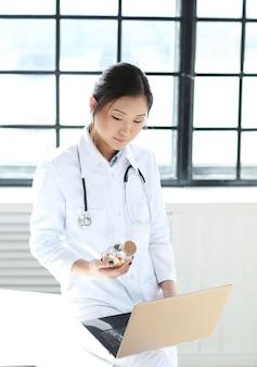 Aziatische vrouwelijke arts, vrouwenspecialist met laptop en pillen