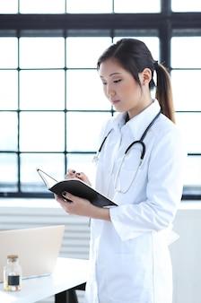 Aziatische vrouwelijke arts, vrouwenspecialist met notitieboekje