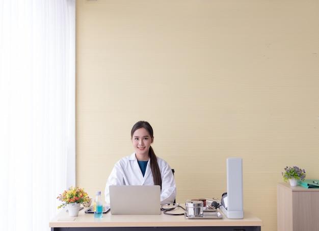 Aziatische vrouwelijke arts zat met een computer en glimlachte gelukkig.