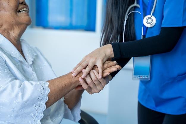 Aziatische vrouwelijke arts zorgt en bespreekt met oudere patiënten in het ziekenhuis, gezondheidszorg en empathieconcept.