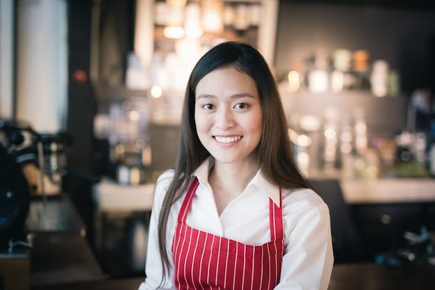 Aziatische vrouwelijke barista draagt rode schort die zich in een koffie bevindt