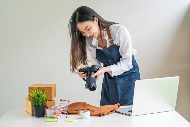 Aziatische vrouwelijke bedrijfseigenaar die een camera vasthoudt om foto's te maken van producten om thuis een laptop en pakketdoos online te verkopen.