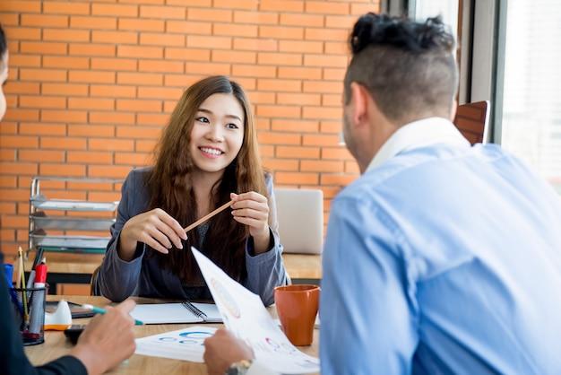 Aziatische vrouwelijke bedrijfsleider die aan haar personeel tijdens de vergadering binnen luistert