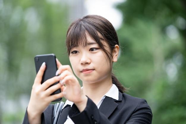 Aziatische vrouwelijke bedrijfspersoon die in openlucht contact opnemen gebruikend een martphone
