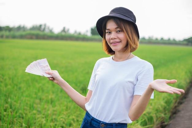 Aziatische vrouwelijke boer in het padieveld met geld