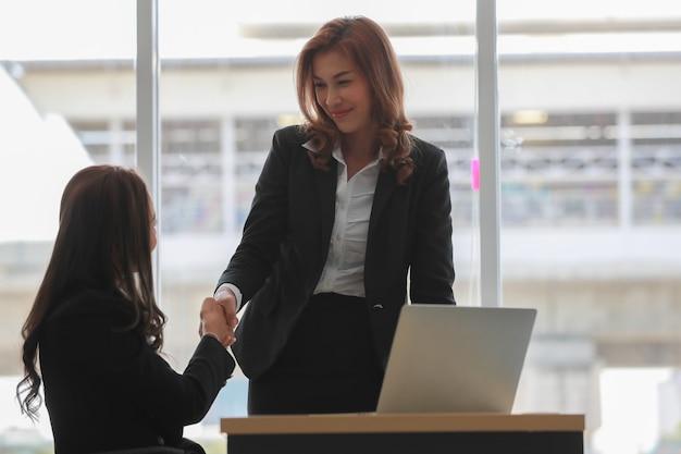 Aziatische vrouwelijke collega's schudden elkaar de hand na slaande deal tegen raam op hedendaagse werkplek