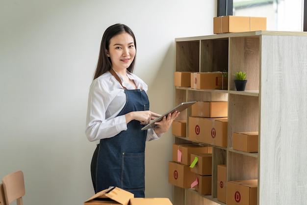 Aziatische vrouwelijke eigenaar van een klein bedrijf die een tablet vasthoudt om pakketten te controleren voordat hij thuis aan klanten levert. camera kijken.
