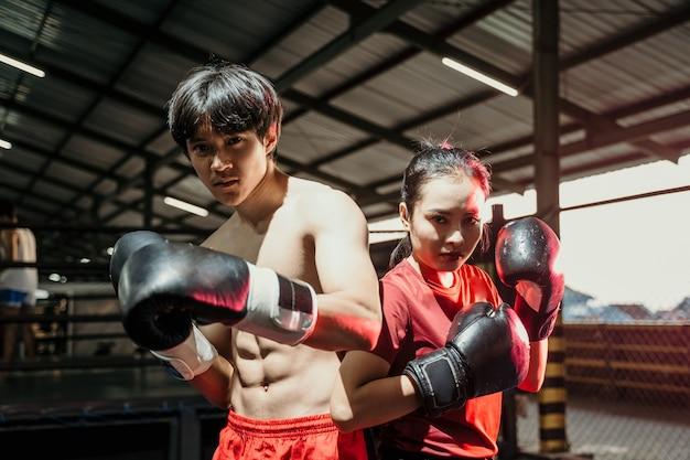 Aziatische vrouwelijke en mannelijke boksers staan in bokshandschoenen met rug aan rug in de boksring