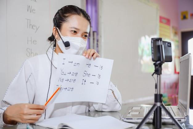 Aziatische vrouwelijke engelse leraar met een masker die studenten leert online op een computerscherm te studeren met behulp van een online videoconferentiesysteem voor onderwijs