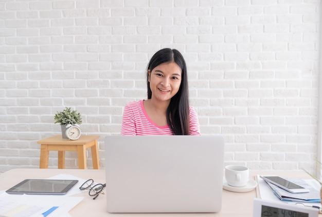 Aziatische vrouwelijke freelancer die aan laptop computer werkt