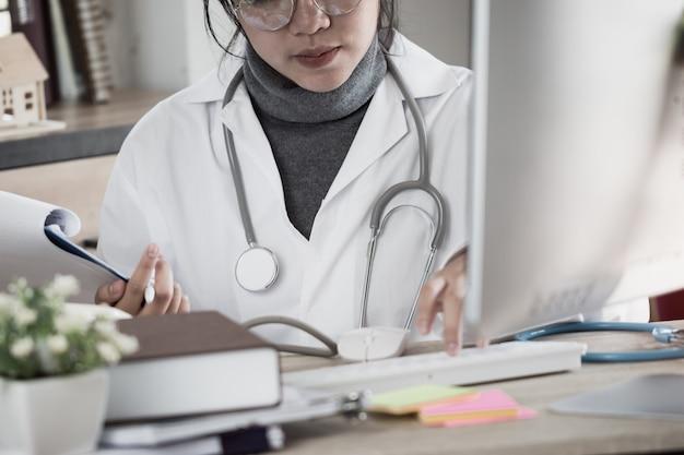 Aziatische vrouwelijke geneeskunde artsen werkende gegevens over laptop computerbureau in kliniek met stethoscoop