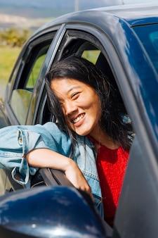 Aziatische vrouwelijke het glimlachen zitting in auto