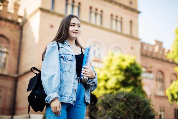 Aziatische vrouwelijke hogeschool of universiteitsstudent. gemengd ras aziatisch jong vrouwenmodel dat schooltas draagt.