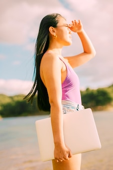 Aziatische vrouwelijke holdingslaptop en zon te bekijken