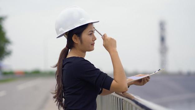 Aziatische vrouwelijke ingenieur die de baan controleert.