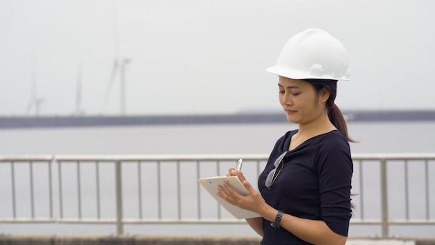 Aziatische vrouwelijke ingenieur die het werk controleert