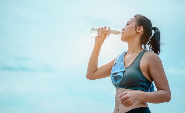 Aziatische vrouwelijke jogger die zoet water drinkt na training jonge atletische vrouw die op de rotsen traint