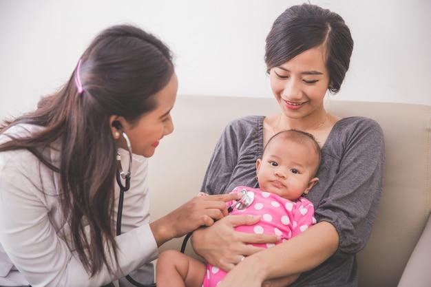 Aziatische vrouwelijke kinderarts die een babymeisje in de schoot van de moeder onderzoekt