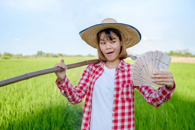 Aziatische vrouwelijke landbouwer in het geld van de padieveldholding