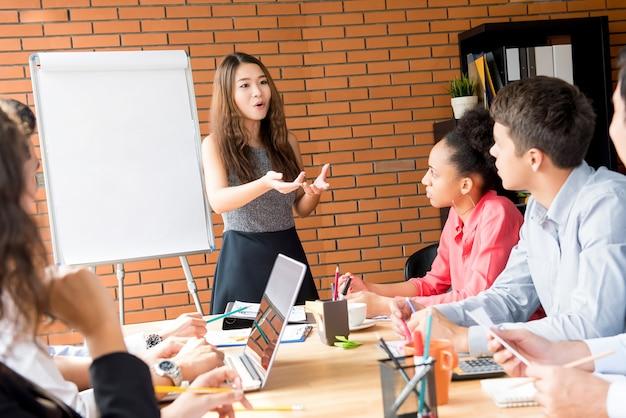 Aziatische vrouwelijke leider presenteren werk de in vergadering