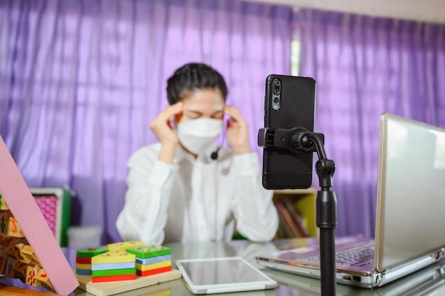 Aziatische vrouwelijke leraar denkt hard en gestrest terwijl ze verdrietig zit ze draagt een masker terwijl ze online studeert. online video voor het onderwijs