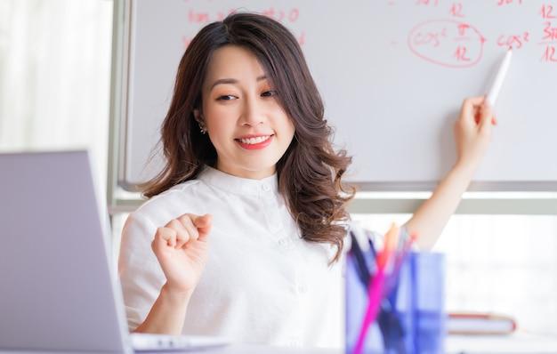 Aziatische vrouwelijke leraar die thuis online onderwijst