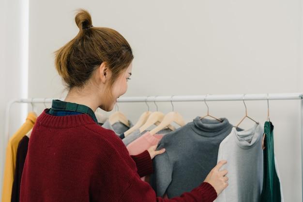 Aziatische vrouwelijke manierontwerper die, kleren werkt controleren controleren