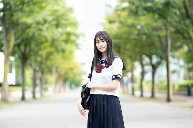 Aziatische vrouwelijke middelbare school student lachend in uniform buitenshuis