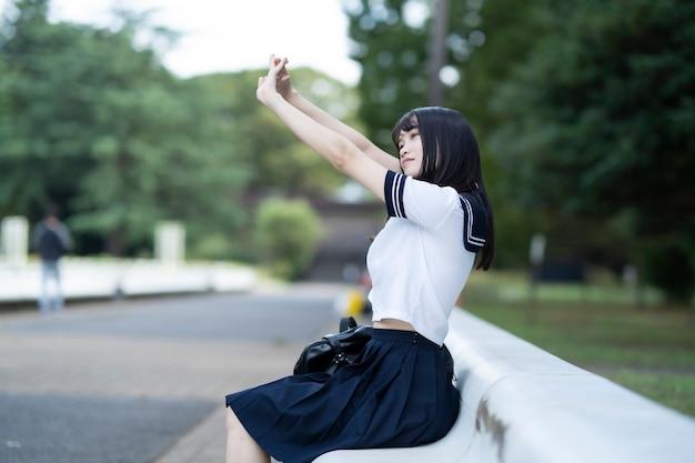 Aziatische vrouwelijke middelbare schoolstudent die en zich bij het park zitten uitrekt