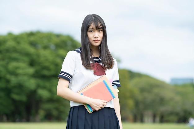 Aziatische vrouwelijke middelbare schoolstudent die in het park studeert
