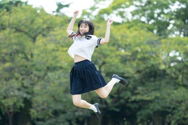 Aziatische vrouwelijke middelbare schoolstudent die met een glimlach in het park dartelt