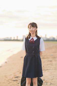 Aziatische vrouwelijke middelbare schoolstudent die op het strand loopt