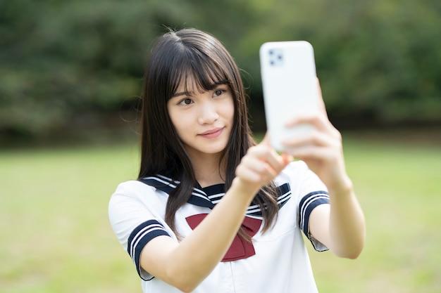 Aziatische vrouwelijke middelbare schoolstudent wat betreft het scherm van de smartphone