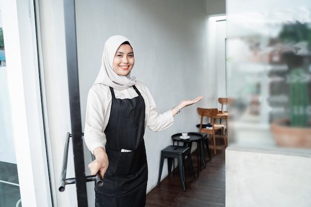 Aziatische vrouwelijke ober nodigt gasten uit om binnen te komen