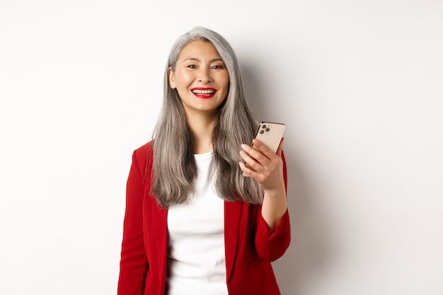 Aziatische vrouwelijke ondernemer in rode blazer met smartphone, glimlachend gelukkig camera, staande op witte achtergrond.