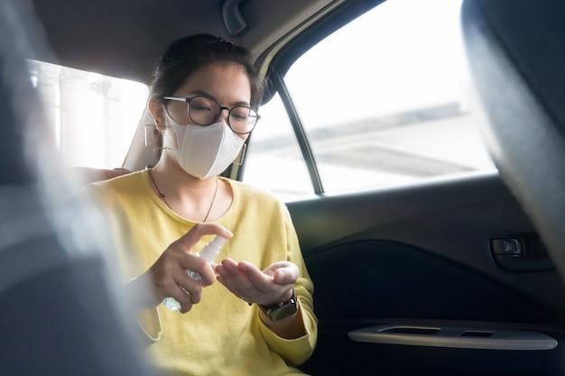 Aziatische vrouwelijke passagier in groen of geel shirt en beschermend masker sproeien desinfecterende alcohol op haar handpalmen en haar handen voor het voorkomen van coronavirus of coronavirus terwijl ze in een auto.