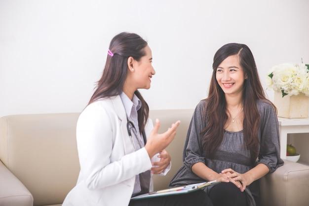 Aziatische vrouwelijke patiënt die een vrouwelijke arts raadpleegt