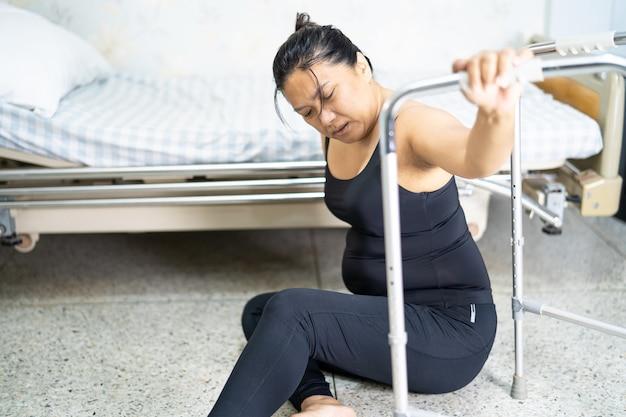 Aziatische vrouwelijke patiënt die in de woonkamer valt vanwege gladde oppervlakken
